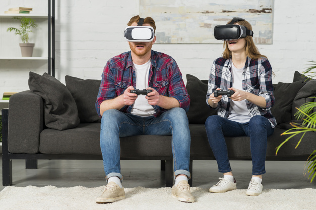 young-couple-sitting-sofa-using-virtual-reality-glasses-playing-video-game-with-joystick_23-2148049009